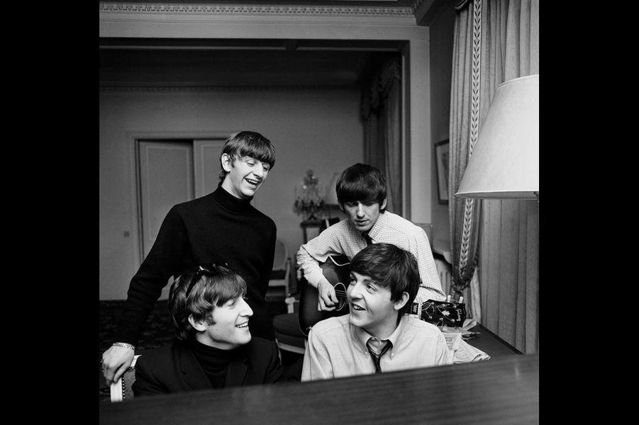 """« Une après-midi dans leur suite, comme il était trop tard pour sortir, mais trop tôt pour se préparer pour le concert, Ringo s'est assis au piano. Paul est arrivé, suivi par John. Alors qu'ils commençaient à jouer quelques notes, Ringo s'est mis en retrait. George est arrivé avec sa guitare. Petit à petit ils sont devenus sérieux, ils ne jouaient plus, ils composaient. Ils étaient totalement absorbés par ce qu'ils faisaient. J'étais devenu invisible.» """" I Feel Fine """" ‐ Exposition des photos des Beatles prises par Harry Benson au George V Du 15 au 30 juin 2014, dans le hall et en face du bar Four Seasons Hotel George V 31 avenue George V, 75008 Paris."""
