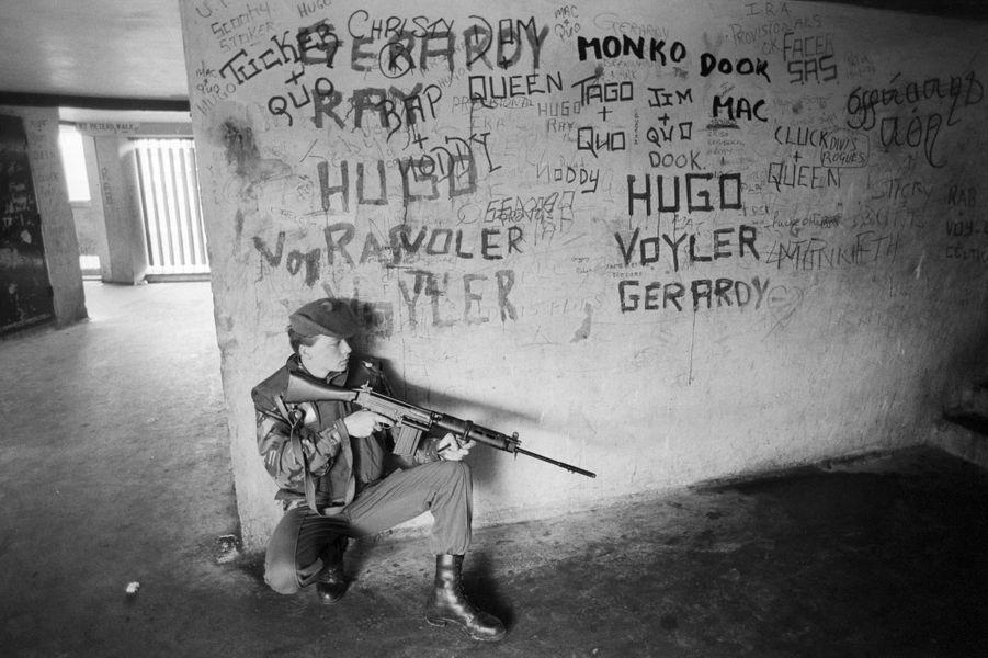Septembre 1979, en IRLANDE du NORD, à BELFAST, le déploiement de l'armée anglaise dans la ville : soldat armé en position de tir dans un couloir d'immeuble d'habitation aux murs graffités.