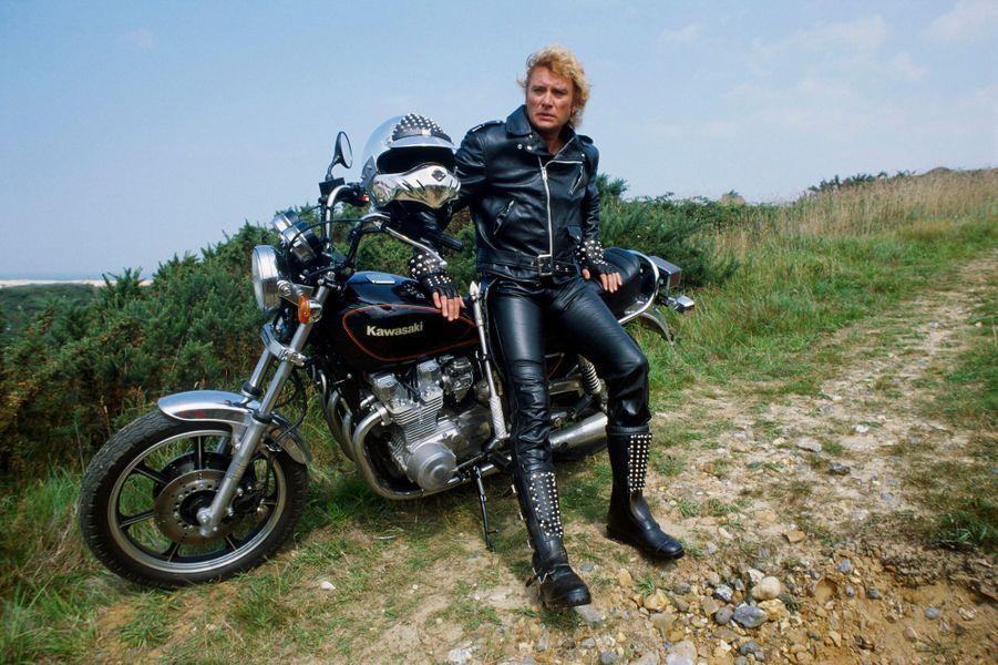 Août 1982 - Johnny HALLYDAY au Touquet pour préparer son show du Palais des Sports : en tenue de motard, look à la Mad Max, pantalon et blouson de cuir noir et bottes cloutées, assis sur une moto Kawasaki, dans les dunes.