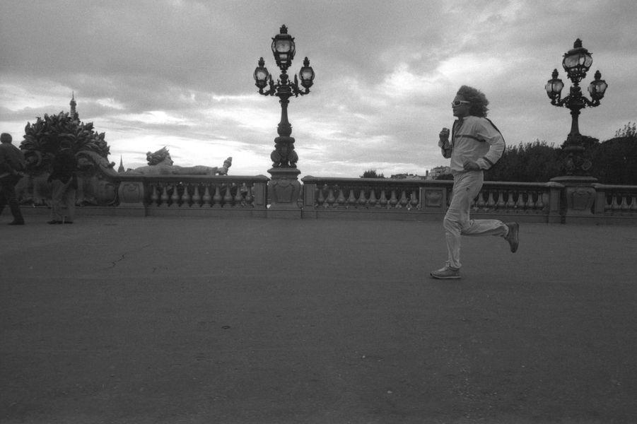 Attitude de Michel POLNAREFF faisant son jogging sur un pont de PARIS.