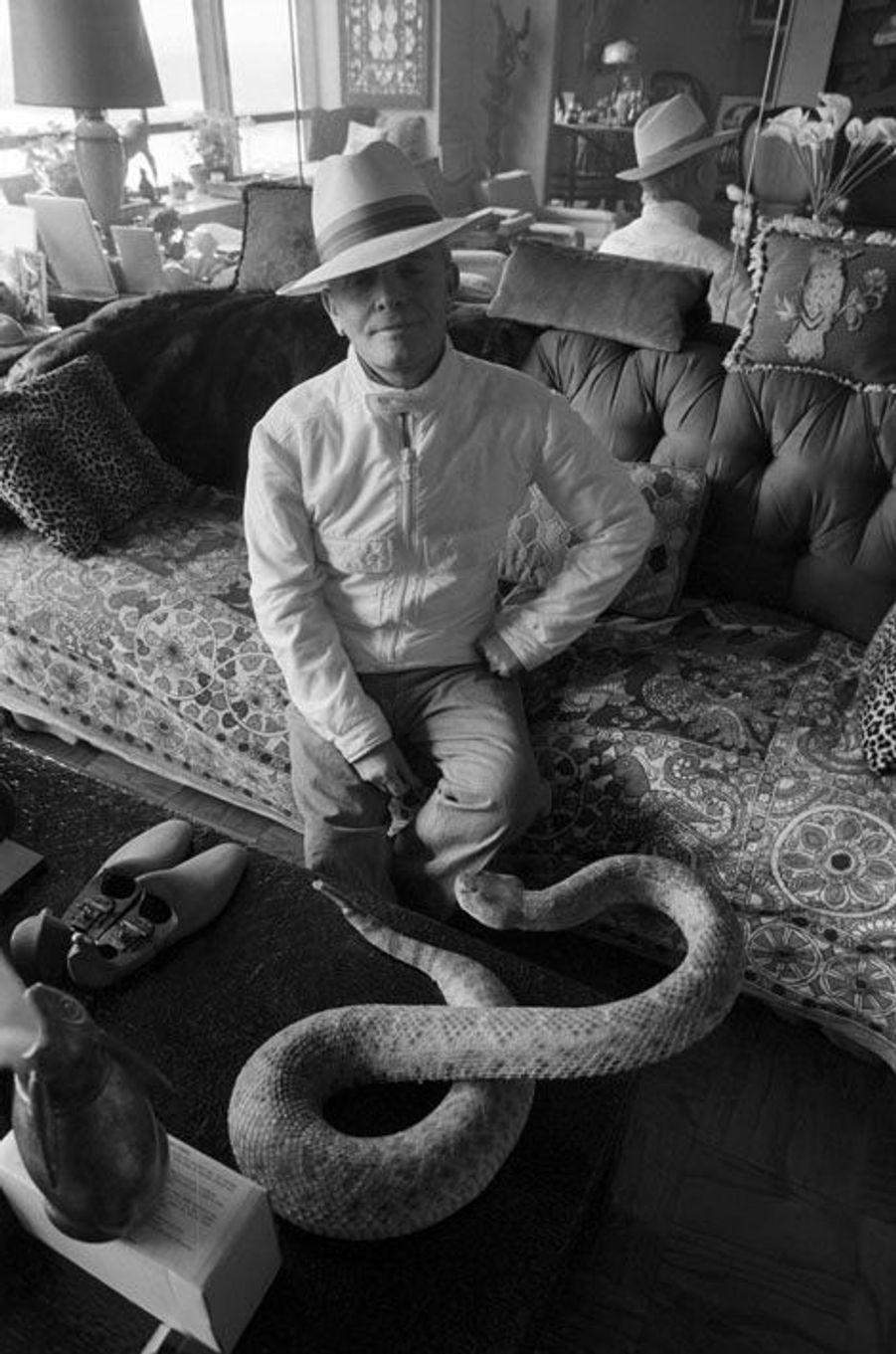 Rendez-vous avec Truman CAPOTE chez lui à New York L'écrivain pose dans son salon assis sur un canapé, coiffé d'un Panama, vêtu d'un petit blouson blanc et d'un jean, la main sur la hanche, devant un serpent à sonnettes empaillé posé sur la table basse.