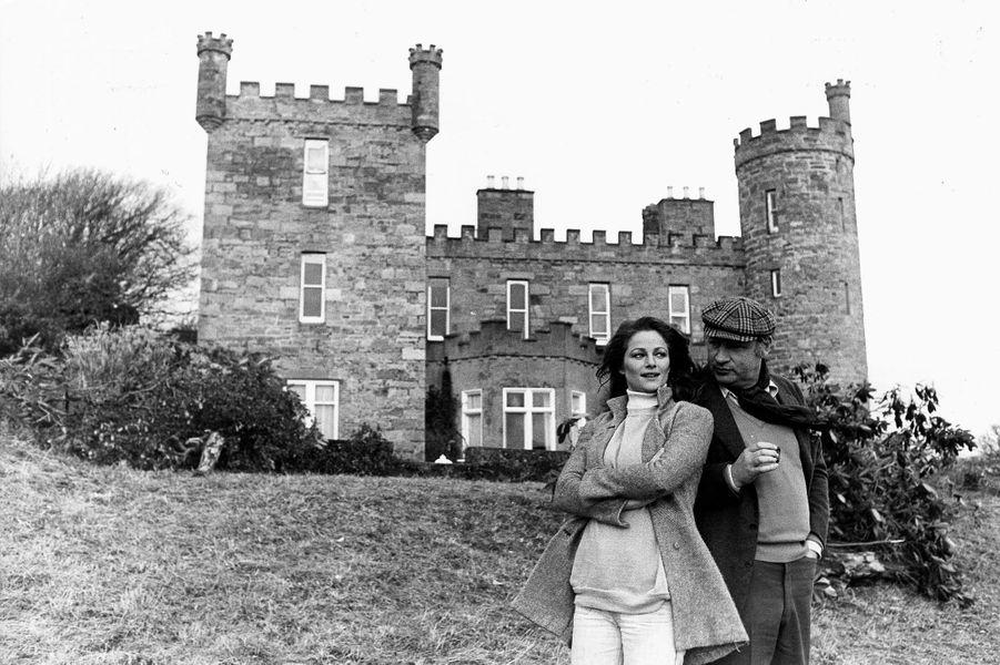"""Attitude souriante de Charlotte RAMPLING appuyée contre Philippe NOIRET fumant un cigare devant le château de MALBURY où se tourne leur film """"Un taxi mauve"""" d'Yves BOISSET."""