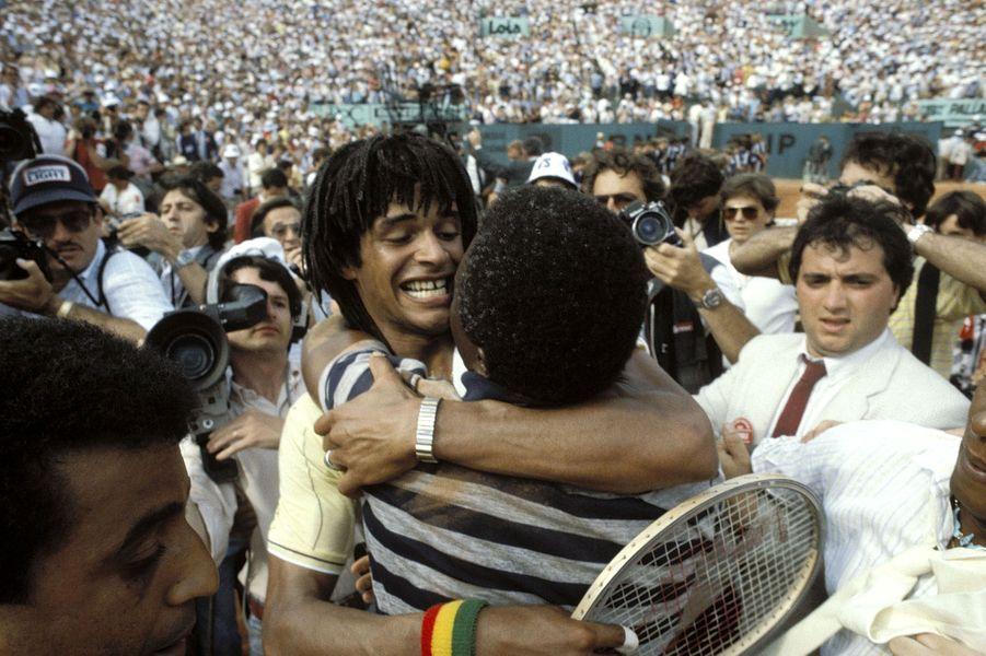 Yannick NOAH remporte la finale de tennis face à Mats WILANDER en trois sets : le joueur dans les bras de son père Zacharie à l'issue du match entourés de nombreuses personnes sur le court central de Roland-Garros.