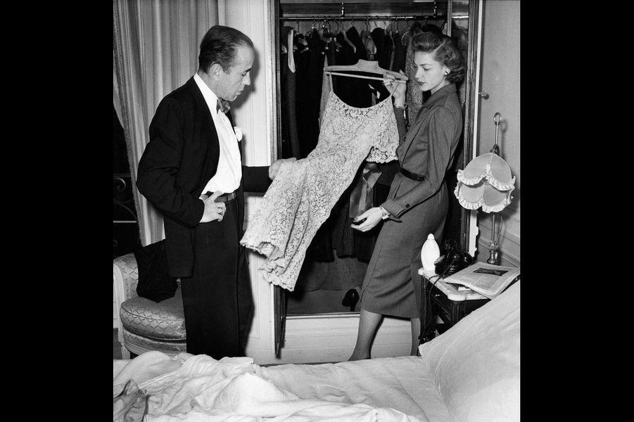"""1951 - Lauren Bacall et Humphrey Bogart sont en vacances à Paris. Bogart veut montrer la Ville Lumière aux plus beaux yeux d'Amérique . Dans leur appartement de l'hôtel Ritz ils se sont efforcés de recréer dès leur arrivée une atmosphère familière. Les murs sont tapissés de photos de leur fils Stephen, et de leur villa de Beverly Hills. Dans l'intimité Humphrey appelle Lauren """" Baby"""" et elle l'appelle """"Bogie"""". Sur la photo Lauren a sorti de ses malles cinq tailleurs, deux robes noires de dîner et un manteau de vison."""