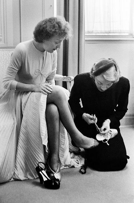 """1952 - Edith Piaf se marie avec Jacques Pills à New York dans la petite église de Saint-Vincent-de-Paul en bas de Manhattan. Au mariage il y avait une dame en noir : Marlene Dietrich. Pendant toute la journée la vedette de l'ange bleu n'a pas quitté l'interprète de la """"Vie en rose"""". Elle fut à la fois sa conseillère, son témoin et son maître de cérémonie. Ici avant de partir pour l'église, Marlene à genoux, fait les dernières retouches en rajoutant des trous à l'aide de ciseaux dans la lanière des chaussures d'Edith Piaf."""