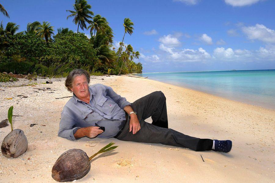 """2008 – Olivier de Kersauson, """"le solitaire des mers du sud"""", sur un atoll des Tuamotu. À 64 ans il aime tout particulièrement ces drôles d'îles formées d'une étroite bande de sable entourant un lagon, sorte de porte entre la terre et l'océan. La Polynésie, il peut en dessiner les moindres passes pour les avoir explorées depuis 1967. Aux antipodes de sa Bretagne adorée, c'est son deuxième port d'attache."""