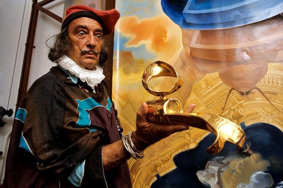 Déguisé en grand d'Espagne, avec collerette à la Velásquez et bracelet oriental, Salvador Dalí présente un objet mystérieux, synthèse du cercle évasé, du cylindre éclaté et de l'instrument de mesure.