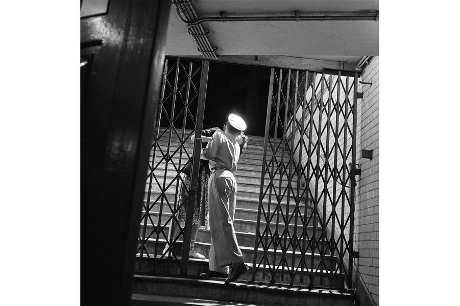 Au moment de fermer la grille d'une station, un employé du métro embrasse sa petite amie. Pris en 1950, la même année que le  célèbre Baiser de l'hôtel de ville de Robert Doisneau,