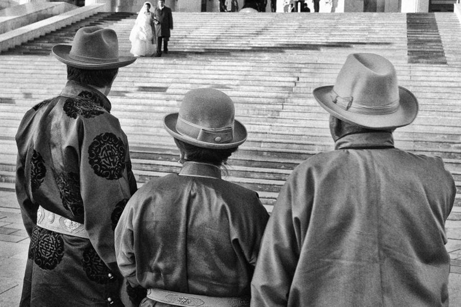 Mongols en habits traditionnels, de dos, regardant des mariés sortir d'un temple.
