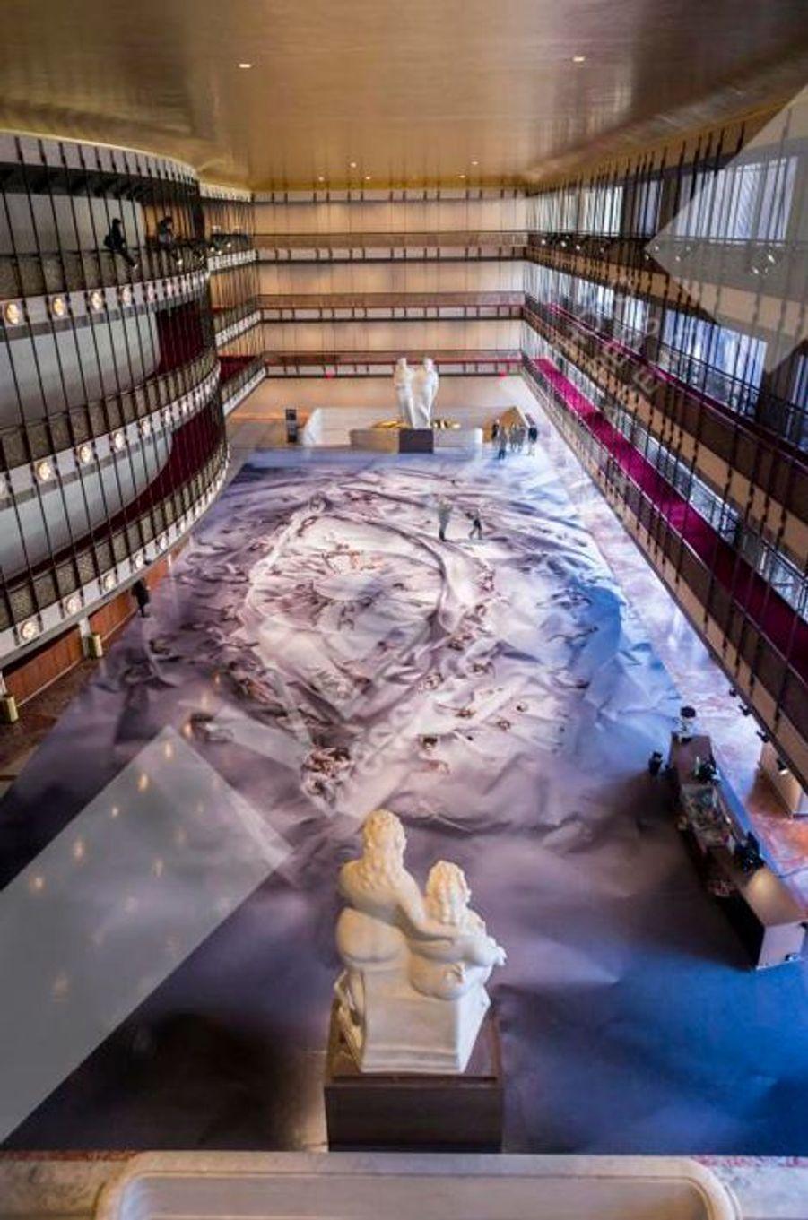 A seulement trente ans, le franco-tunisien JR a créé une forme d'art nouvelle dont la démesure est pourtant toujours à l'échelle humaine. Il en livre un nouvel exemple en collaboration avec le New York City Ballet. JR a investi le David H. Koch Theater dans le cadre de la seconde édition des Art Series new-yorkaises. Au coeur de son installation, un oeil immense, qui occupe tout la surface vaste hall du théâtre. Il est composé des 80 danseurs et ballerines du ballet, interprétant une chorégraphie immobile dans les plis d'une feuille de papier froissé. Inévitablement, les visiteurs sont tentés de se mêler aux danseurs, preuve que l'art de JR est, malgré son gigantisme, est le plus accueillant qui soit.
