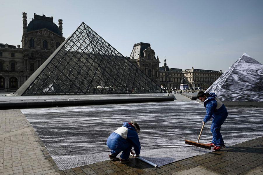 Cette semaine, l'artiste JRet des bénévoles ont installé un collage géant pour les 20 ans de la pyramide du Louvre.