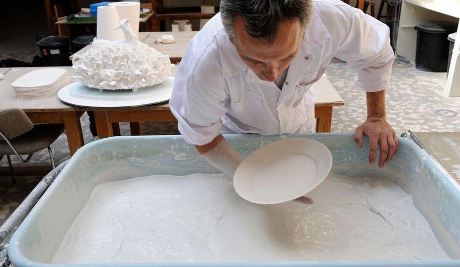 Dans l'atelier d'émaillage, l'artisanat est un sport de haut niveau : tout est dans le geste. Cela implique la répétition à l'infini du mouvement parfait, celui qui évite toute coulure sur les pièces. Michel Roué, poseur d'émail depuis 1979, nous démontre que le savoir-faire, issu d'une expérience transmise depuis 1740, peut être une chorégraphie étourdissante.