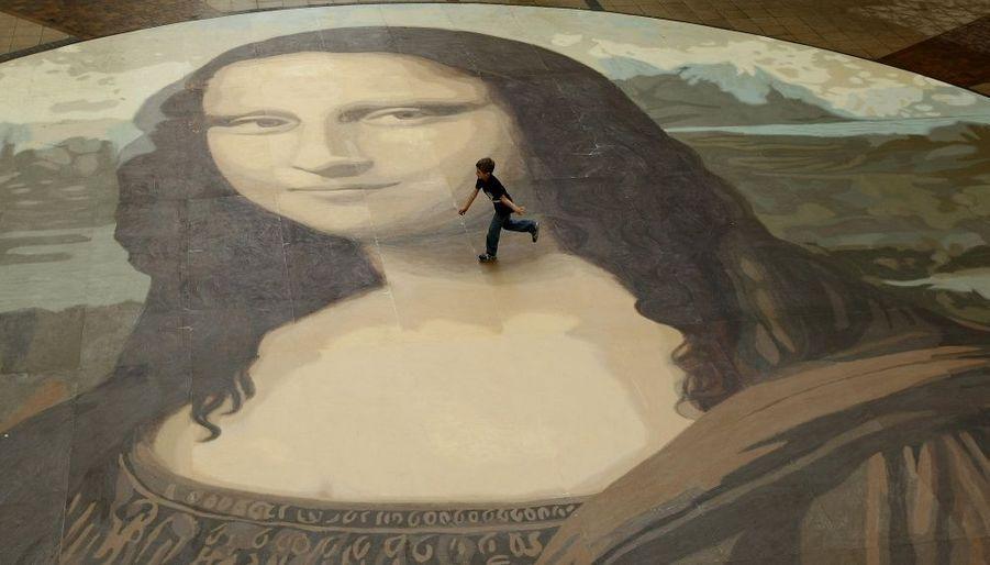 A Wrexham, au Pays de Galles, un enfant cour sur une reproduction géante de la Joconde (240 m2) installée dans un centre commercial.