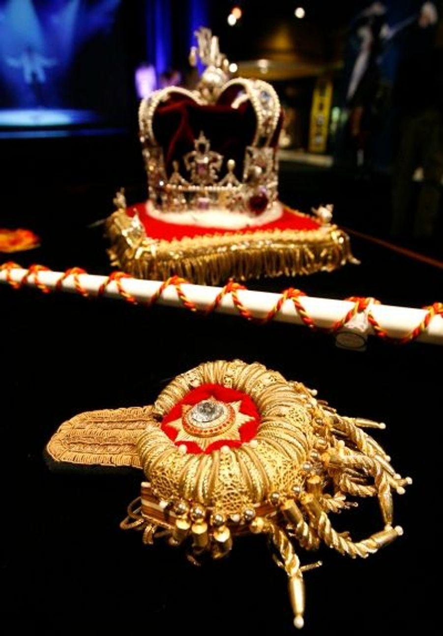 Une épaulette de style militaire, un sceptre de représentation et une couronne.