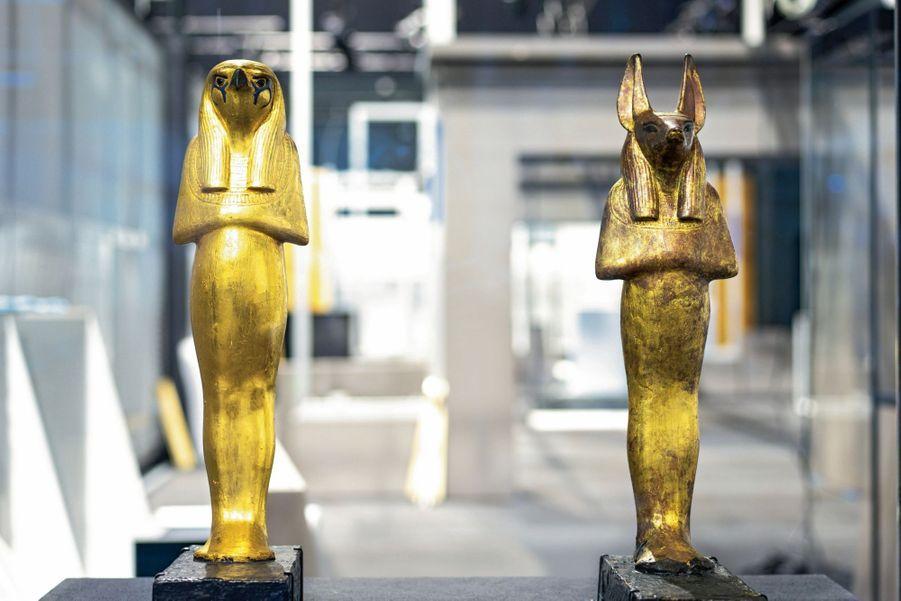Figures en bois doré du dieu Horus (hauteur 56,8 centimètres, à g.) et de son fils Douamoutef (hauteur 56,8 centimètres)