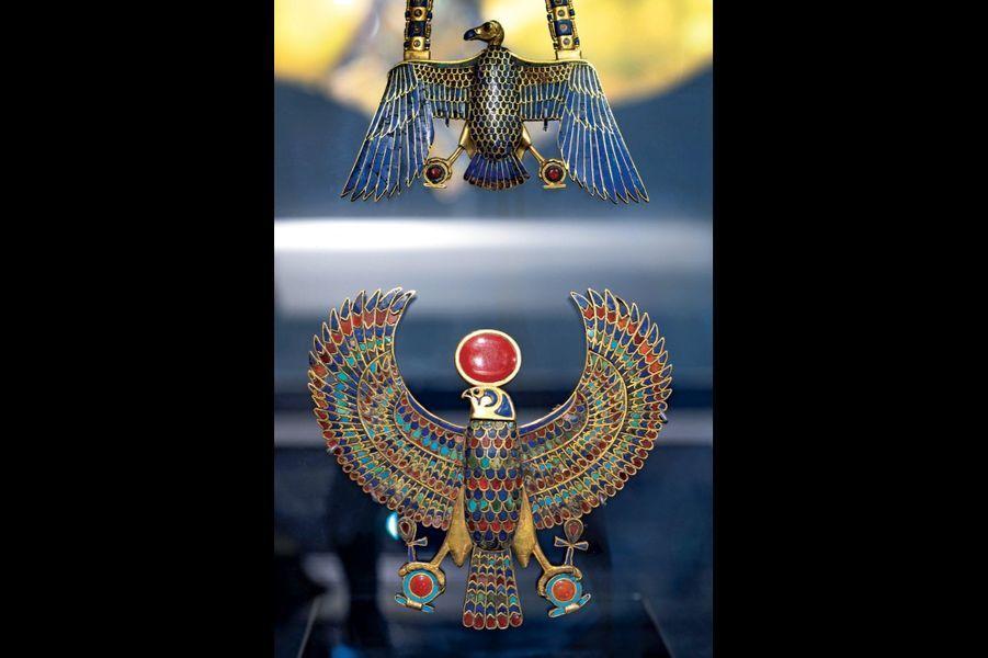 Deux pectoraux en or incrustés de lapis-lazuli, turquoises, cornalines et verre. Celui du haut représente Nekhbet (largeur 11 centimètres), le second est à l'effigie d'Horus (largeur 12,6 centimètres).