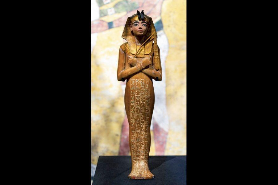 Statuette funéraire du roi à coiffe némès. Bois, gesso, feuille d'or et bronze. Hauteur 53,6 centimètres.