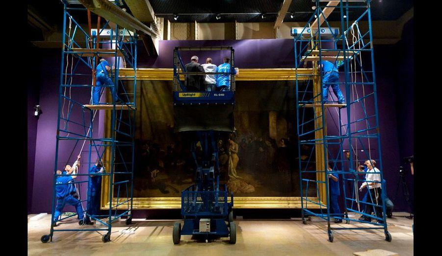 """""""L'atelier du peintre"""" est en passe d'être fixé sur sa nouvelle cimaise. Le violet des murs d'exposition a été choisi avec un soin tout particulier : leur couleur ne doit pas se heurter à la seule star de cette fête du regard, l'oeuvre."""