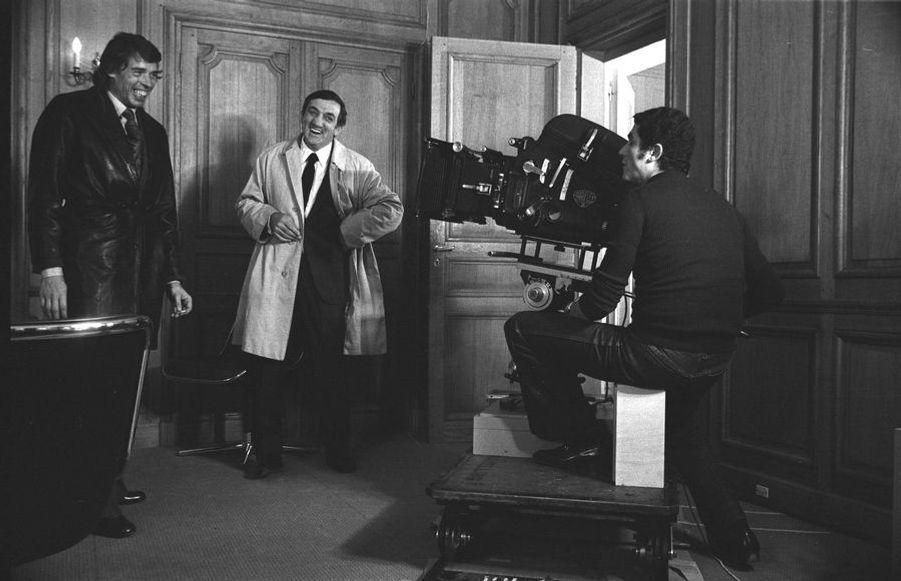 Claude Lelouch, Jacques Brel & Lino Ventura, par Christian Gibey (1936-2012). La complicité de Claude Lelouch avec Jacques Brel et Lino Ventura contribuera à la réussite de L'aventure c'est l'aventure, le film où il les dirige, en 1972. A l'origine, le rôle tenu par Brel avait été prévu pour Jean-Louis Trintignant, qui l'a refusé. Lino, lui, a accepté le sien sans hésiter : il rêvait depuis dix ans de travailler avec Lelouch.LOT N°009 - Tirage postérieur sur papier baryté - Edition 1/1 - 53 x 80 cm - Encadrement bois noir et passe-partout tournant.