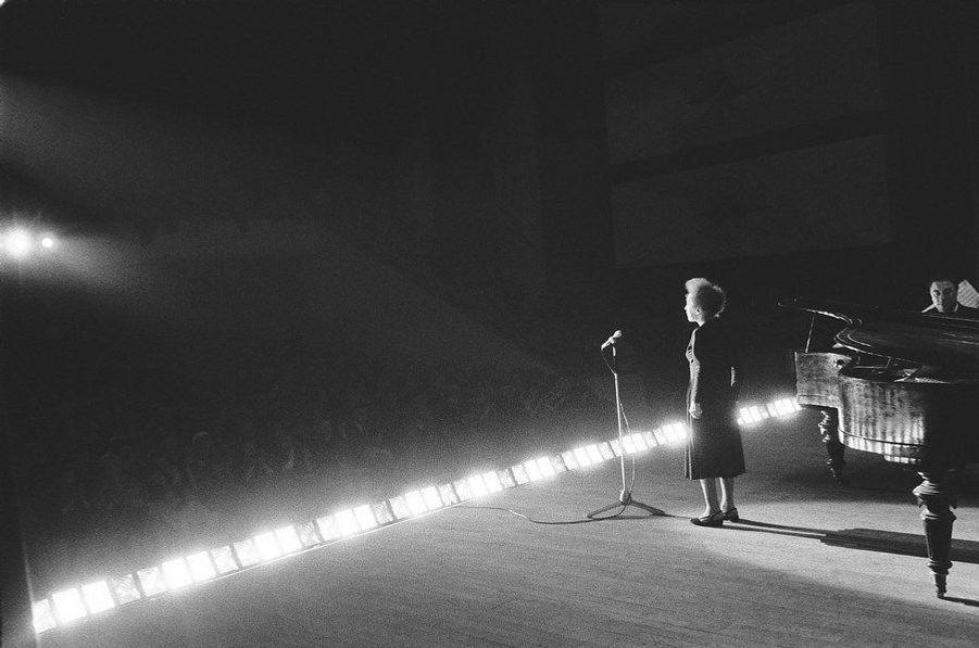 Edith Piaf, par Roger Picherie (1929-2004). Le 21 décembre 1960, Édith Piaf chante à Nancy. Affectée par sa rupture avec Georges Moustaki, épuisée par une vie entière d'excès, torturée par une polyarthrite invalidante, elle tient le coup grâce à des piqûres de morphine. Elle vient à peine d'avoir 45 ans, elle en paraît trente de plus. Elle est bouleversante.LOT N°063 - Tirage postérieur sur papier baryté - Edition 1/1 - 53 x 80 cm - Encadrement bois noir et passe-partout tournant.