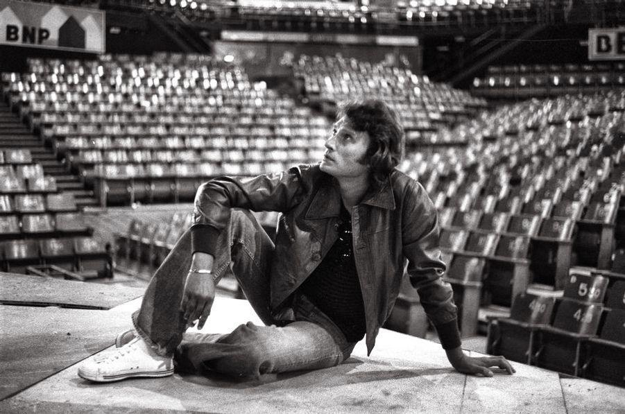 Johnny Hallyday, par Benjamin Auger (1942-2002). Seize ans après son premier 45-tours, l'indéboulonnable idole des jeunes continue de régner sur le rock français. Le 28 septembre 1976, Johnny Hallyday contemple la salle où il chantera ce soir : celle du Palais des Sports, où il a conquis ses galons de star au temps des yéyés. Il va s'y produire un mois entier, devant plus de 200 000 fans.LOT N°044 - Tirage postérieur sur papier baryté - Edition 1/1 - 53 x 80 cm - Encadrement bois noir et passe-partout tournant.