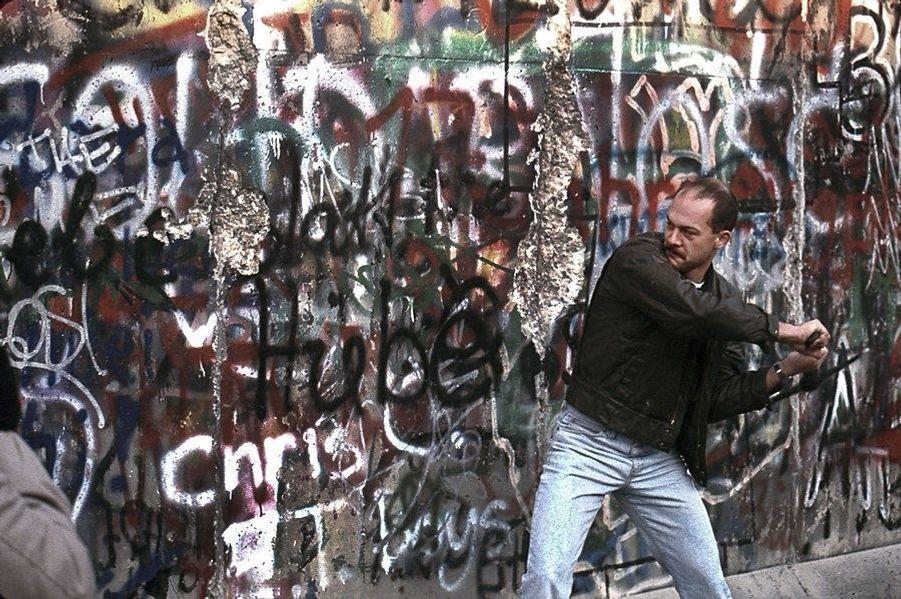 La chute du mur de Berlin, par Benoît Gysembergh (1954-2013). Un homme casse le Mur à coups de pioche. Novembre 1989.LOT N°068 - Tirage postérieur sur papier baryté - Edition 1/1 - 52 x 78 cm - Encadrement bois noir et passe-partout 5 cm tournant.