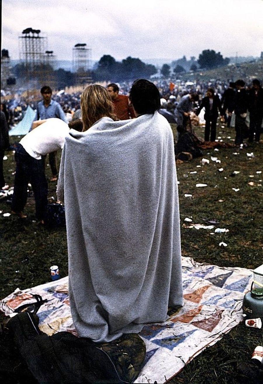 Le Festival de Woodstock, par Georges Beutter (1944-2011). Un couple enlacé dans une couverture lors du Festival de Woodstock. Août 1969.LOT N°049 - Tirage postérieur sur papier baryté - Edition 1/1 - 52 x 78 cm - Encadrement bois noir et passe-partout 5 cm tournant.
