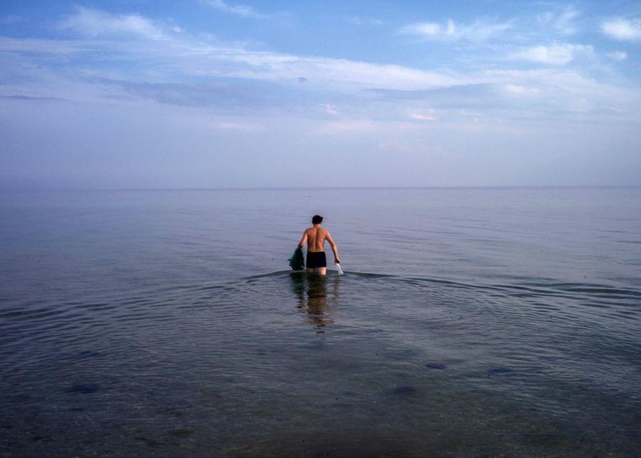 Un touriste se baigne dans la Mer Noire, sur l'île de Dzharylhach, en Ukraine, le 20 août 2016.