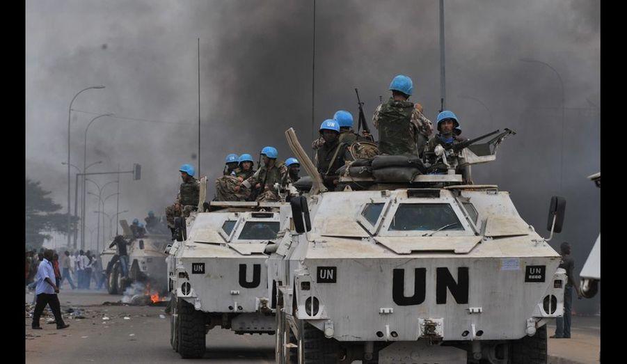 Quartier d'Abobo, Abidjan. Convoi de casques bleus devant une manifestation pro-Ouattara. À l'arrière-plan, la fumée de pneus incendiés. Les forces de sécurité fidèles à Laurent Gbagbo ont tiré au gaz lacrymogène sur les manifestants. Les élections du 28 novembre, remportées par Ouattara, avaient entraîné le pays dans une véritable crise politique et économique. Photo Issouf Sanogo / Agence France-Presse.