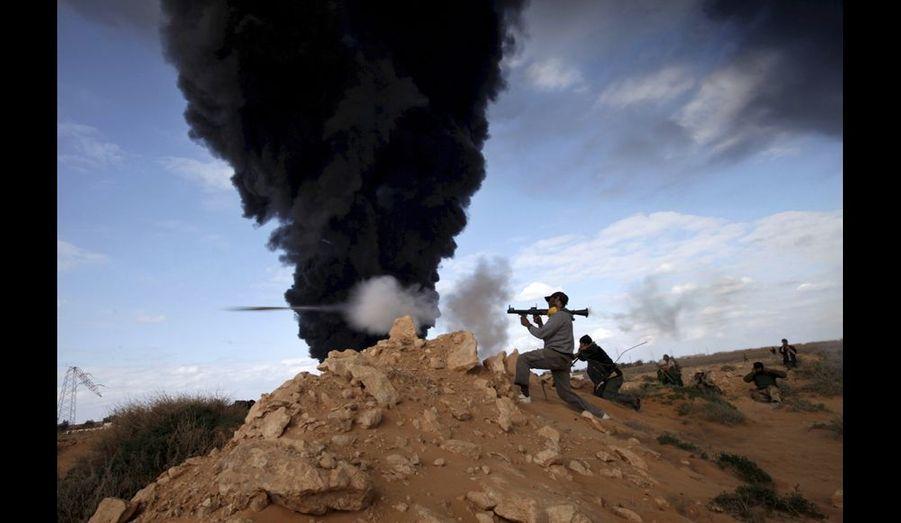 Ras Lanouf, Libye. Des combattants anti-Kadhafi tirent au lance-roquettes sur les forces régulières. Ils ont de plus en plus de mal à résister à la pression de l'armée qui est, en plus, assistée par des mercenaires d'Afrique noire. Hier, en fin d'après-midi, écrasés par les tirs d'artillerie et de chars, ils ont commencé à se replier dans le désert. Photo Kuni Takahashi/Polaris/Starface pour Paris Match.