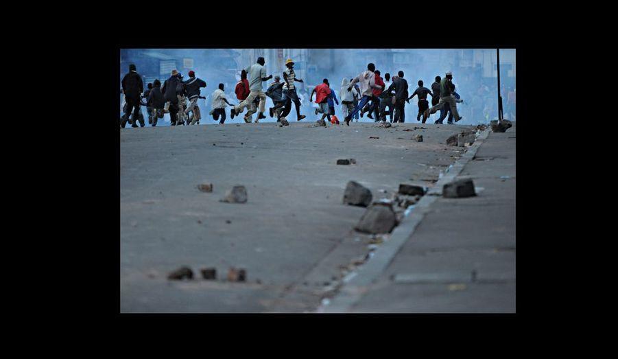 Partisans d¹Andry Rajoelina, maire d¹Antananarivo, fuyant les tirs de gaz lacrymogènes, après une confrontation entre manifestants et forces del¹ordre.