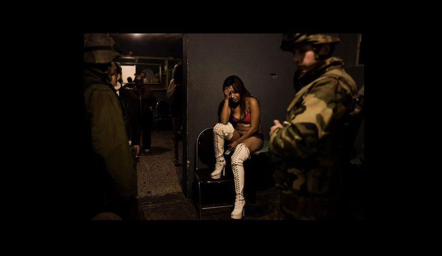"""Une danseuse """"topless"""" interrogée par des militaires lors d'une opération de contrôle dans les night-clubs de Ciudad Juarez."""