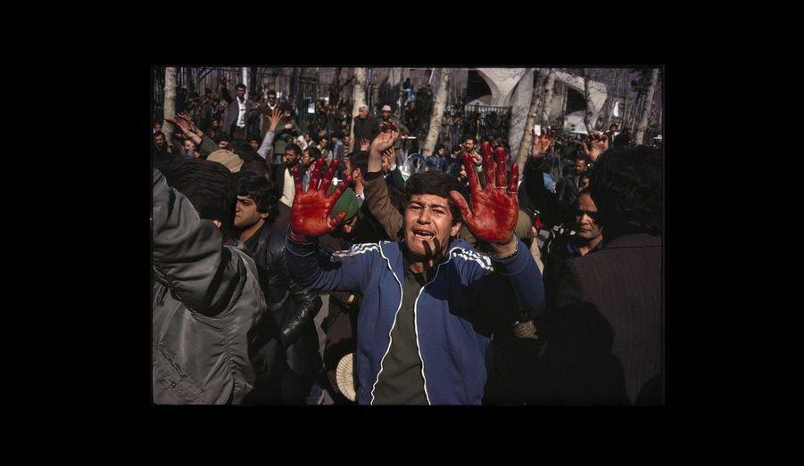 Près de l¹université, un manifestant exhibe ses mains maculées du sang d¹un « martyr ».