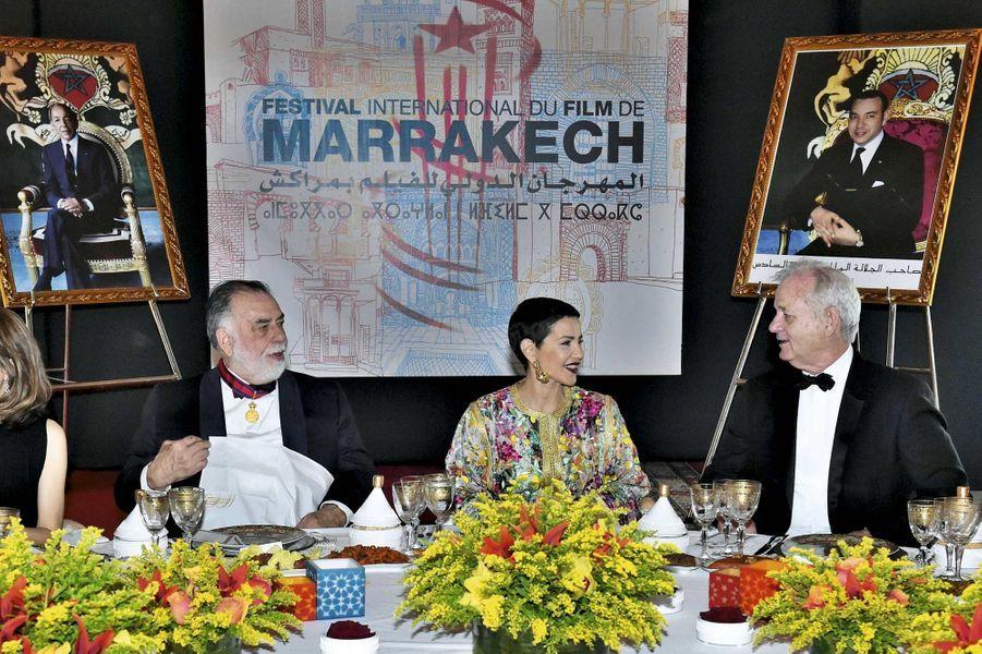 Leroi du Marocavait décidé de maintenir, en dépit desattaques du 13 novembreà Paris, le 15e Festival -international du film de Marrakech. La « capitale du Sud » -célèbre, chaque année, la fusion entre le pays et le monde du cinéma. Confronté aux attentats du 11 septembre 2001, -Mohammed VI avait déjà pris la même décision. Il a chargé Faïçal Laraïchi, vice-président délégué, d'en assurer le succès. Défi relevé. La séquence gastronomique a été improvisée par unCoppolahabitué des superproductions : il a préparé des spaghettis tomate-basilic pour 110 invités, réunis pour le dîner Dior. Le metteur en scène s'est mis aux fourneaux à 20 h 45. A 22 h 30, il servait les deux premières assiettes, sous les vivats.Entourée par Francis Ford Coppola (à g.) et Bill Murray, la princesse Lalla Meryem préside le dîner royal, et non le dîner Dior comme cela a été imprimé par erreur dans le magazine.