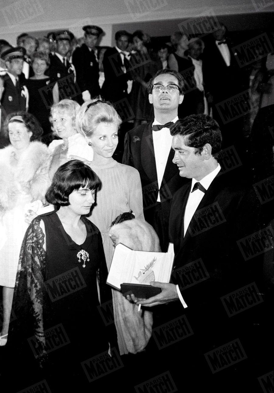 """Agnès Varda et Jacques Demy au 17ème Festival de Cannes, en 1964, avec la Palme d'or que le réalisateur vient de recevoir pour son film """"Les parapluies de Cherbourg""""."""