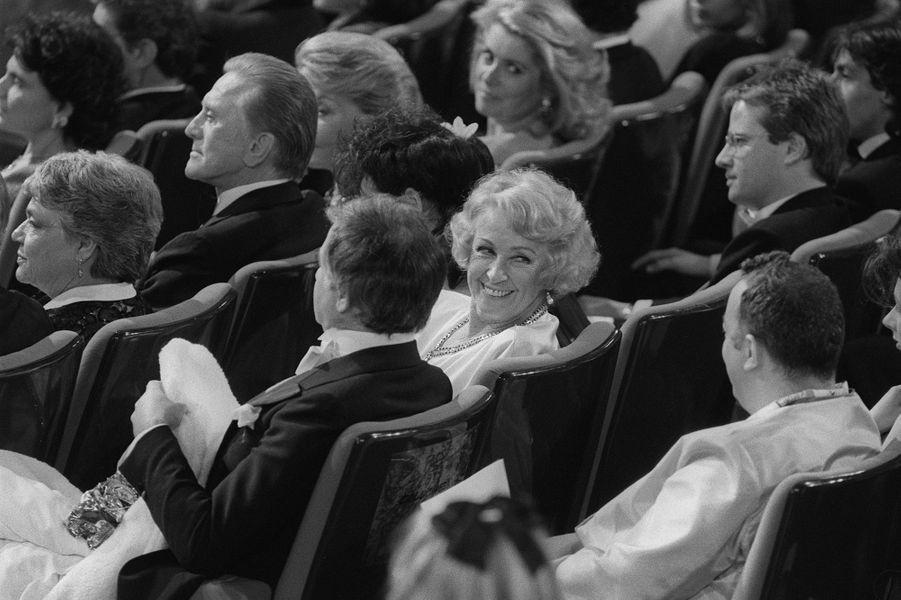 L'actrice Danielle Darrieux sourit après avoir reçu un César d'Honneur, lors de la 10ème cérémonie des Césars au Théâtre de l'Empire, le 02 mars 1985, à Paris. Elle est entourée de Simone Signoret, Kirk Douglas, Catherine Deneuve, Christophe Lambert, Coluche.