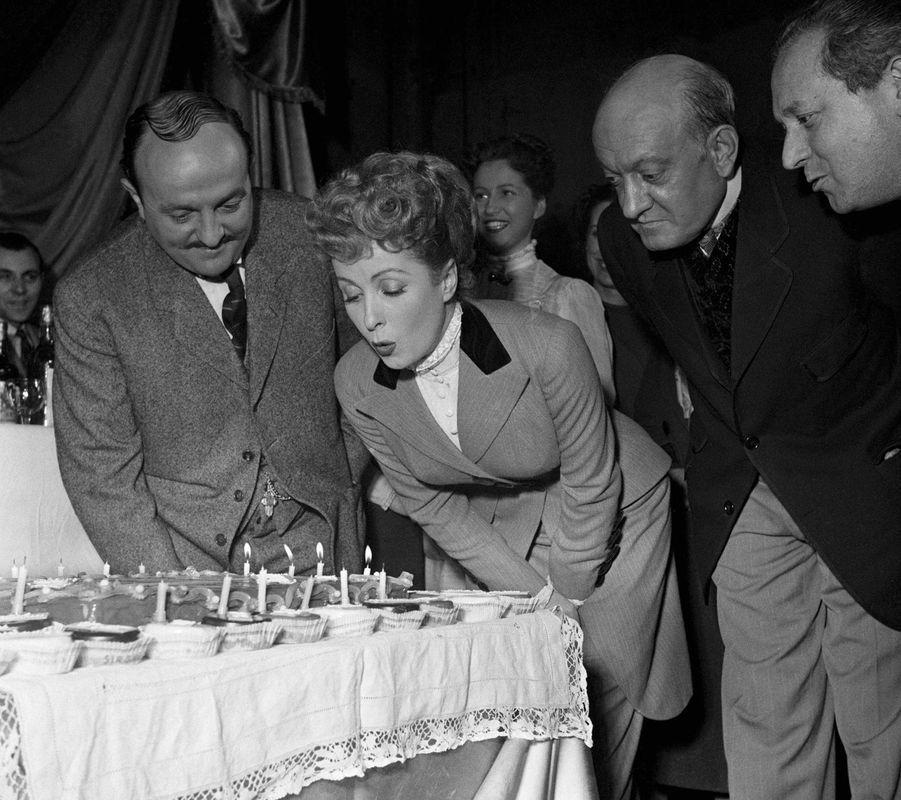 """Danielle Darrieux fête son anniversaire avec Bernard Blier et Yves Deniaud en 1951 sur le tournage de """"La maison Bonnadieu""""."""