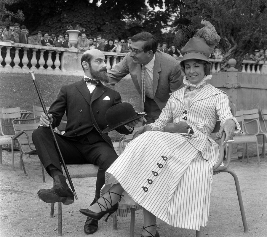 """Le cinéaste Claude Chabrol (C) donne des indications à ses acteurs Charles Denner (G) et Danielle Darrieux (D) lors du tournage de son film """"Landru"""", le 12 juin 1962 à Paris."""