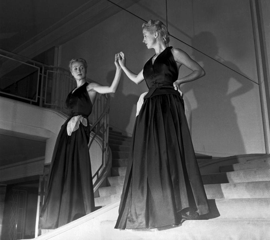 Attitude de Danielle DARRIEUX en robe du soir dos nu sans manches, se regardant dans un miroir dans un escalier.