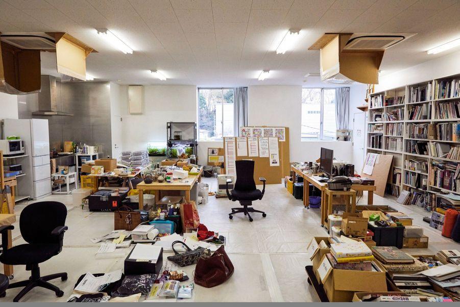 Sa pièce à vivre, avec le bureau et, à gauche, le coin cuisine. Interdiction de montrer le carton qui lui sert de couchette.