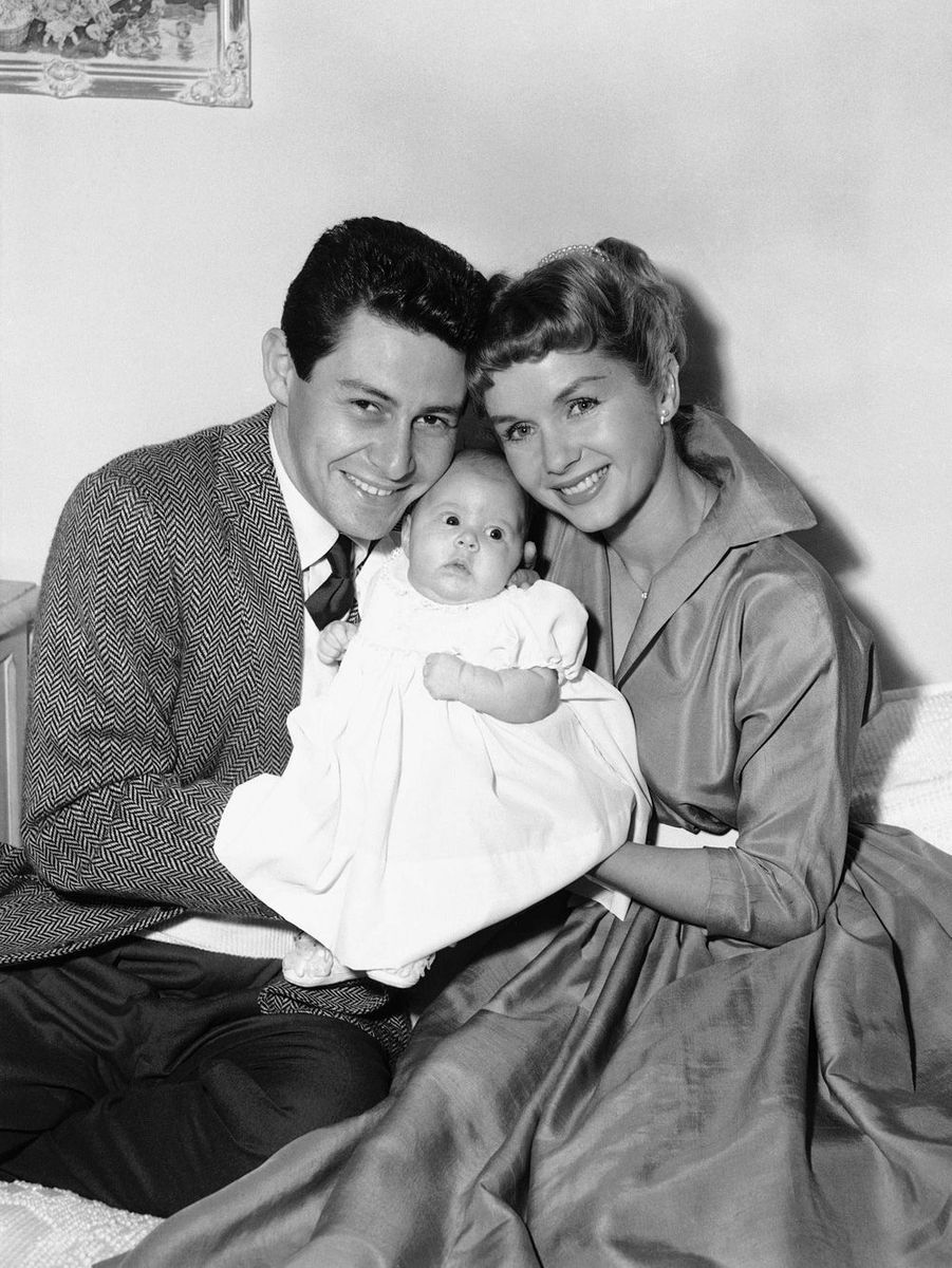Eddie Fisher et Debbie Reynolds portent la petite Carrie dans leurs bras.