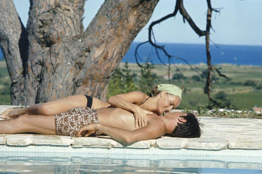 """Tournage du film """"La piscine"""" de Jacques DERAY dans le décor d'une somptueuse villa aux environs de Saint-Tropez pourvue d'une immense piscine : Romy SCHNEIDER souriante allongée auprès d'Alain DELON au bord de la piscine, tous deux en maillot de bain."""