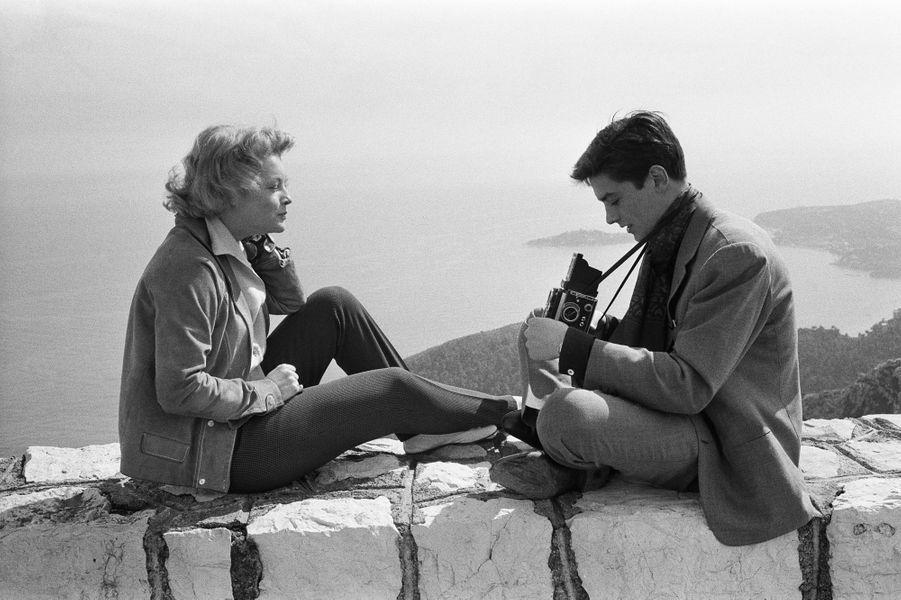Un mois après leurs fiançailles officielles, Romy SCHNEIDER et Alain DELON passent Pâques sur la Côte d'Azur : Alain 24 ans assis en tailleur sur un muret dominant la mer photographiant Romy assise en face de lui.