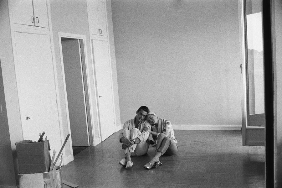 Alain DELON vient d'acheter un appartement au troisième étage d'un immeuble futuriste, le palais Eraclès, sur le port de MONACO : le couple assis par terre dans l'appartement vide après la fin des travaux, tous deux jambes repliées, côte à côte, Romy la tête posée sur l'épaule d'Alain.