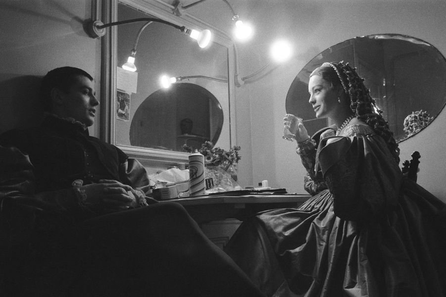 """La pièce """"Dommage qu'elle soit une p..."""" mise en scène par Luchino VISCONTI au théâtre de Paris : Romy SCHNEIDER un verre d'eau à la main assise devant la coiffeuse de sa loge, discutant avec Alain DELON tous deux en costumes de scène."""