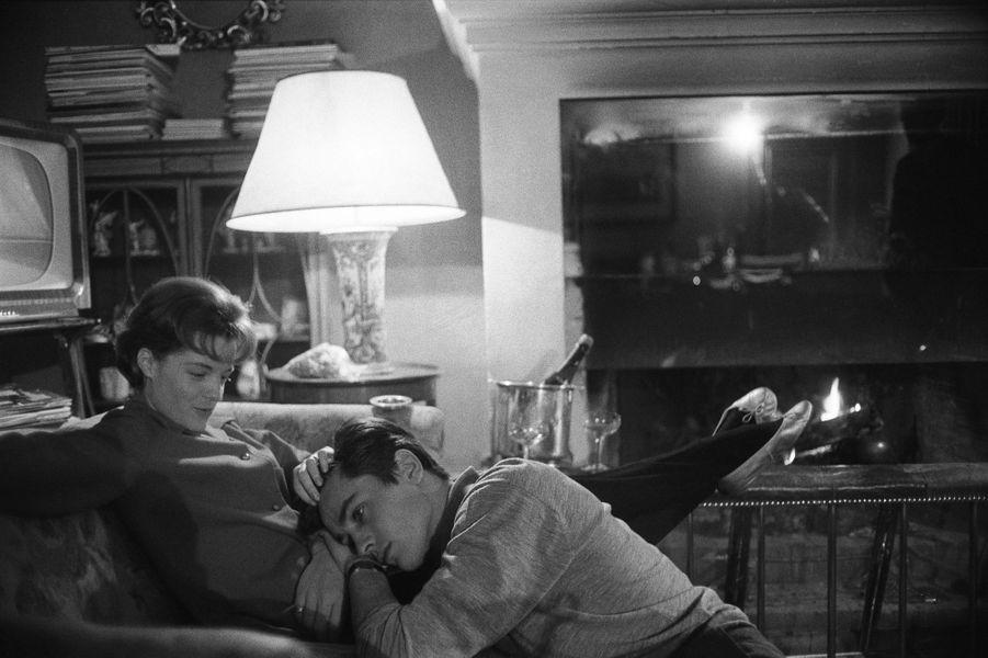 Romy SCHNEIDER et Alain DELON dans leur hôtel particulier de l'avenue de Messine à PARIS : Romy assise sur un canapé dans le salon, caressant la tête d'Alain posée sur ses jambes, l'acteur assis à ses pieds.