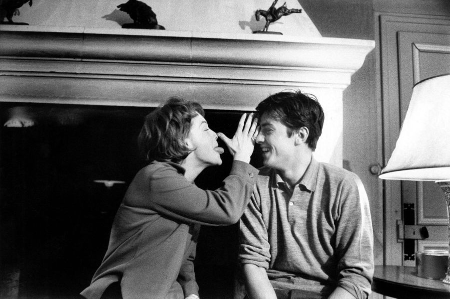 Romy SCHNEIDER et Alain DELON dans leur hôtel particulier de l'avenue de Messine à PARIS : plan de profil de Romy tirant la langue et faisant un pied de nez à Alain riant, tous deux assis devant la cheminée du salon.