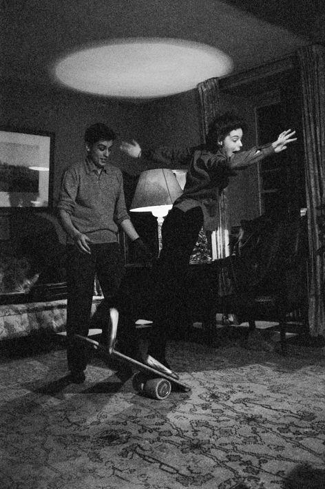Romy SCHNEIDER et Alain DELON dans leur hôtel particulier de l'avenue de Messine à PARIS : Alain regardant Romy perdant l'équilibre alors qu'elle se tenait debout sur une planche posée sur un cylindre.
