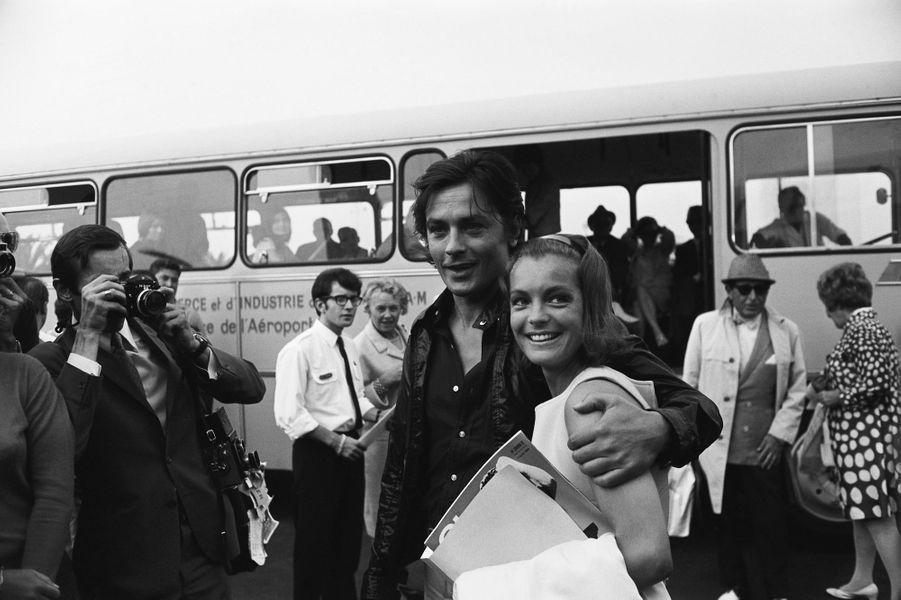 Alain DELON souriant serrant contre lui Romy SCHNEIDER qu'il est venu accueillir à l'aéroport de NICE sous les flashs des photographes.