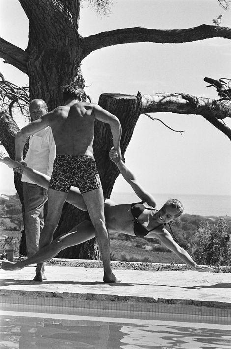 """Tournage du film """"La piscine"""" de Jacques DERAY dans le décor d'une somptueuse villa aux environs de Saint-Tropez pourvue d'une immense piscine : Alain DELON de dos portant à bout de bras Romy SCHNEIDER par une jambe et un bras avant de la jeter dans la piscine."""